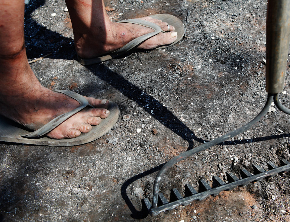 Photo - Lori Turner's dirt covered feet as she holds a rake and stands on ash covered ground where her home at 6000 NE 63 was destroyed when wildfires ravaged land and property that stretched from NE 50 on the south to Hefner Road on the north.  The fire extended from Sooner Road to Midwest Blvd.    Photo taken Wednesday, Aug. 31, 2011. Photo by Jim Beckel, The Oklahoman