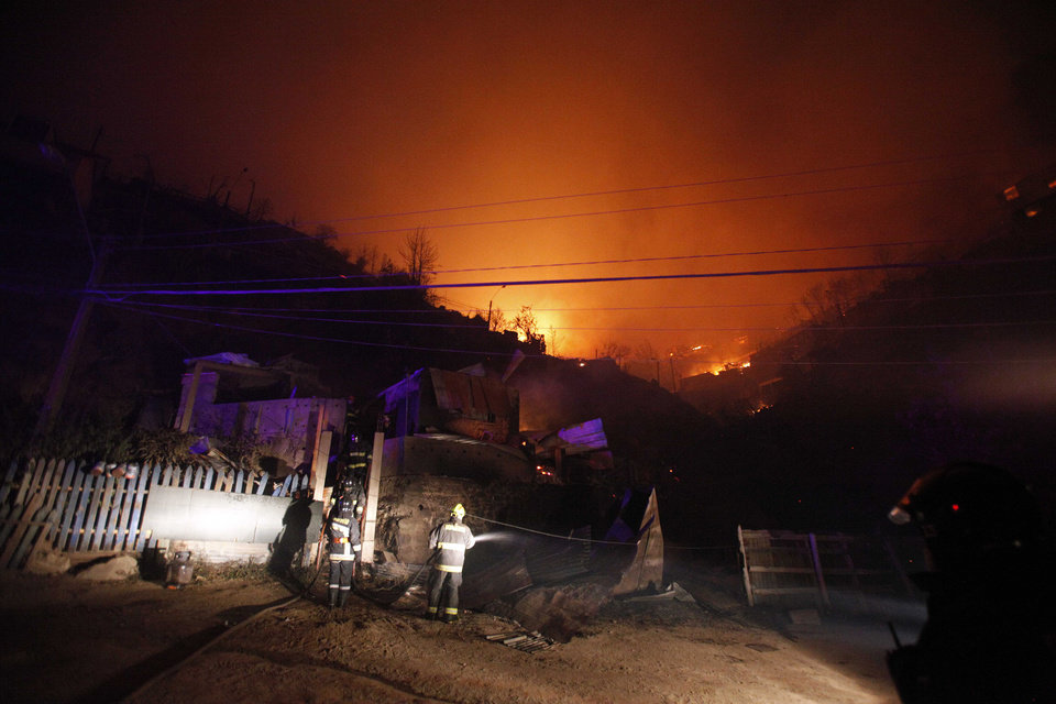 Photo - A group of firefighters stand next to destroyed homes as a forest fire rages towards urban areas in the city of Valparaiso, Chile, Sunday April 13, 2014. Authorities say the first fire has destroyed at least 150 homes and is forcing evacuations.( AP Photo/ Luis Hidalgo)