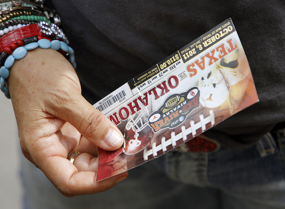 An Oklahoma fan holds their ticket during the Red River Rivalry college football game between the University of Oklahoma Sooners (OU) and the University of Texas Longhorns (UT) at the Cotton Bowl in Dallas, Saturday, Oct. 8, 2011. Photo by Chris Landsberger, The Oklahoman