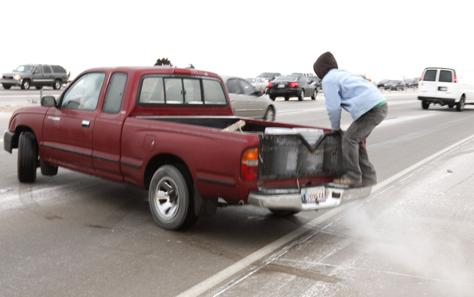 Photo - A passenger jumps on the bed of a pickup Thursday after it slid off the side of Hefner Parkway in Oklahoma City. Photos By Paul Hellstern, The Oklahoman  Online: View more weather photos and submit your own weather photos at NewsOK.com/weather.