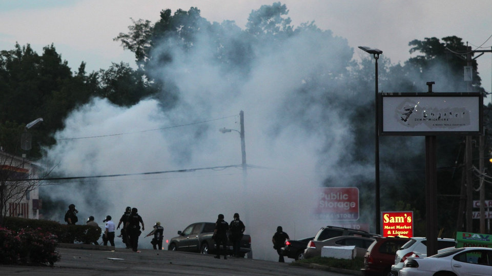 Photo - Tactical officers fire tear gas on Monday, Aug. 11, 2014, in Ferguson, Mo. Authorities in Ferguson used tear gas and rubber bullets to try to disperse a large crowd Monday night that had gathered at the site of a burned-out convenience store damaged a night earlier, when many businesses in the area were looted. (AP Photo/St. Louis Post-Dispatch, Robert Cohen)  EDWARDSVILLE INTELLIGENCER OUT; THE ALTON TELEGRAPH OUT