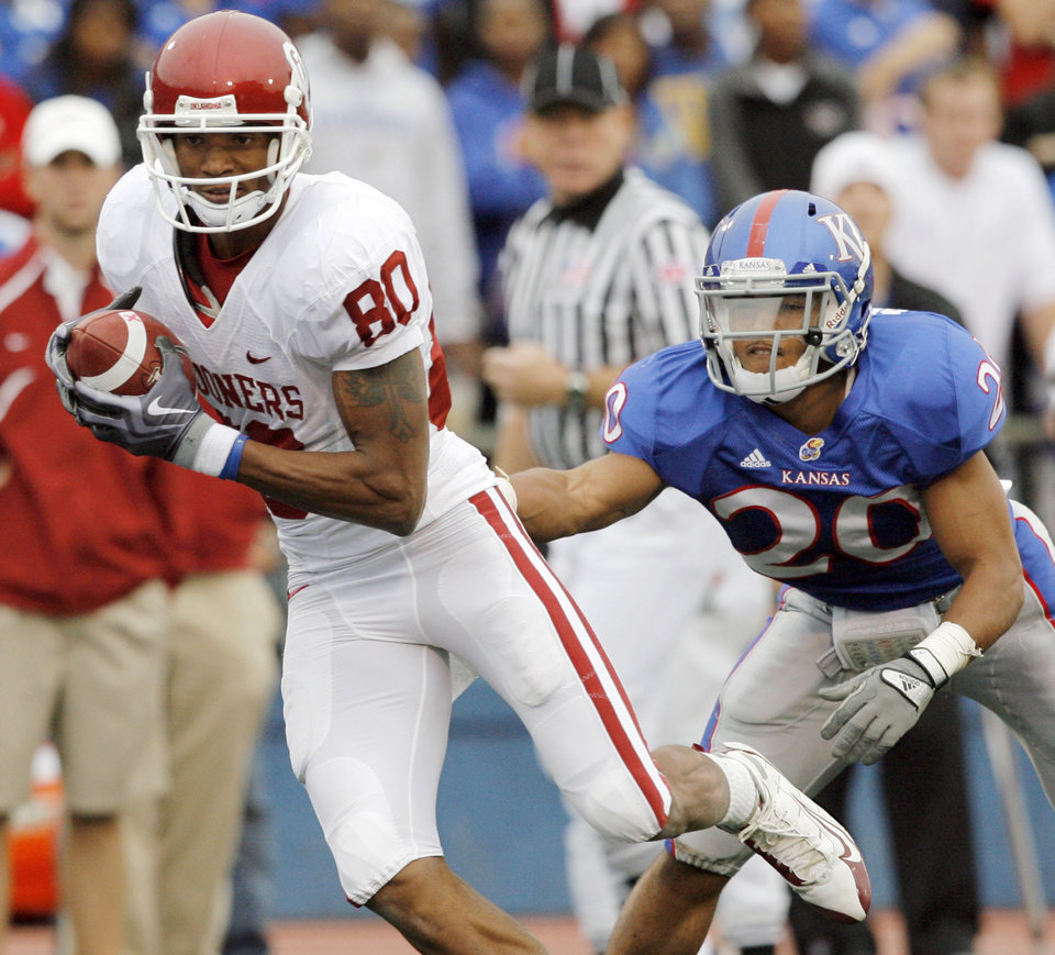 Photo - OU's Adron Tennell (80) breaks away from KU's D.J. Beshears (20) on a touchdown reception during the third quarter of the college football game between the University of Oklahoma Sooners (OU) and the University of Kansas Jayhawks (KU) on Saturday, Oct. 24, 2009, in Lawrence, Kan. OU won, 35-13. Photo by Nate Billings, The Oklahoman