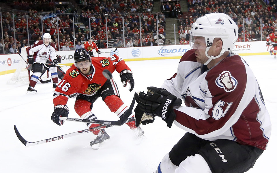 Photo - Chicago Blackhawks center Marcus Kruger (16) and Colorado Avalanche defenseman Andre Benoit (61) battle for a loose puck during the first period of an NHL hockey game Tuesday, March 4, 2014, in Chicago. (AP Photo/Charles Rex Arbogast)