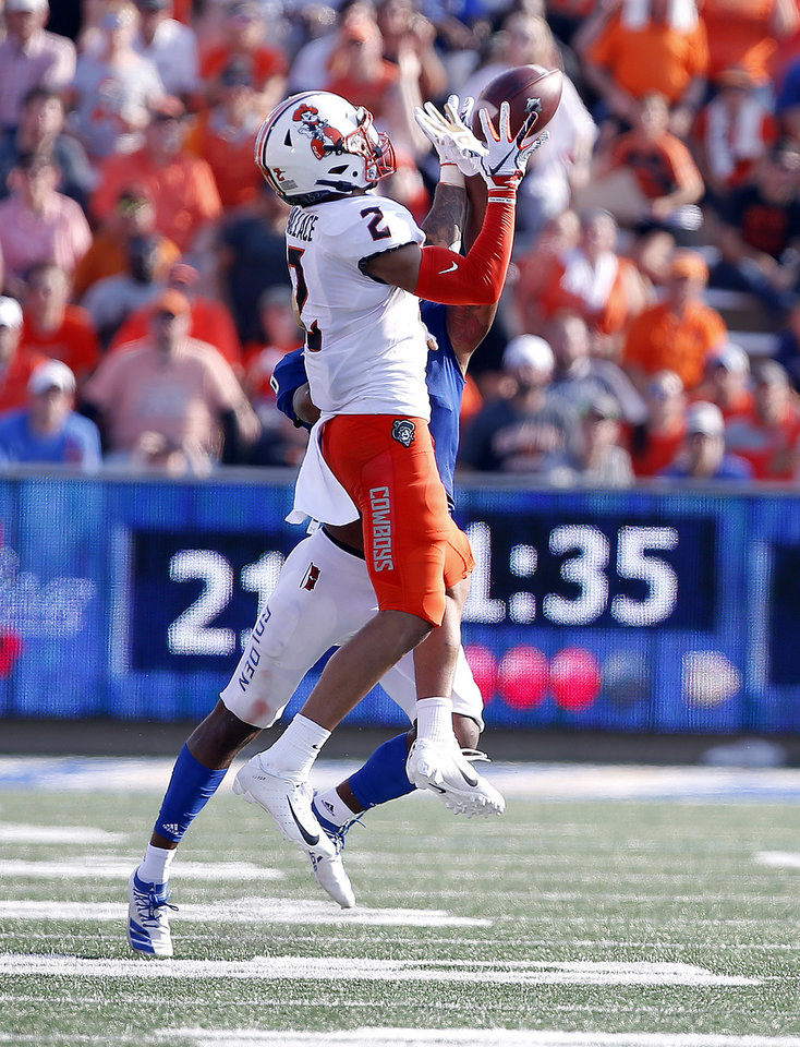 Photo - Oklahoma State's Tylan Wallace (2) catches a pass as Tulsa's Brandon Johnson (8) defends during a college football game between the Oklahoma State University Cowboys (OSU) and the University of Tulsa Golden Hurricane (TU) at H.A. Chapman Stadium in Tulsa, Okla., Saturday, Sept. 14, 2019. Wallace scored a touchdown on the play. [Sarah Phipps/The Oklahoman]