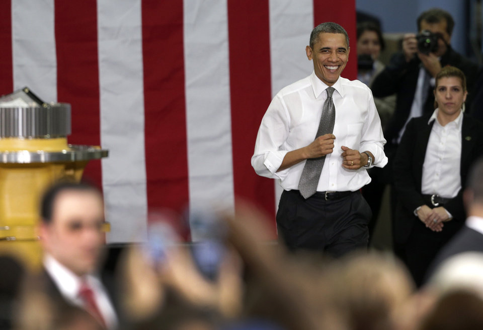 Photo - President Barack Obama runs to the stage before speaking to workers and guests at the Linamar Corporation plant in Arden, N.C., Wednesday, Feb. 13, 2013, as he travels after delivering his State of the Union address Tuesday. (AP Photo/Chuck Burton)