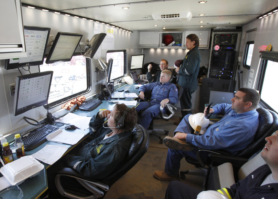 Photo - FILE- In this file photo made on Wednesday, July 27, 2011, engineers and site workers for Range resources monitor computer displays and watch out the window of the mobile command post of the hydraulic fracturing operation in Claysville, Pa. Using computers, engineers can direct drill bits from command centers thousands of miles away. This reduces drilling costs. (AP Photo/Keith Srakocic, File)