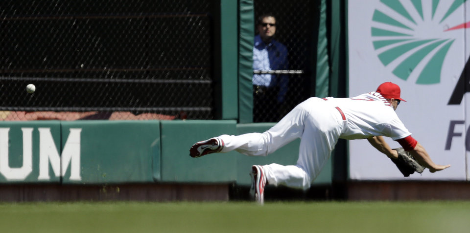 Photo - St. Louis Cardinals left fielder Matt Holliday dives but cannot catch a ball hit for a triple by Cincinnati Reds' Billy Hamilton during the first inning of a baseball game Wednesday, April 9, 2014, in St. Louis. (AP Photo/Jeff Roberson)