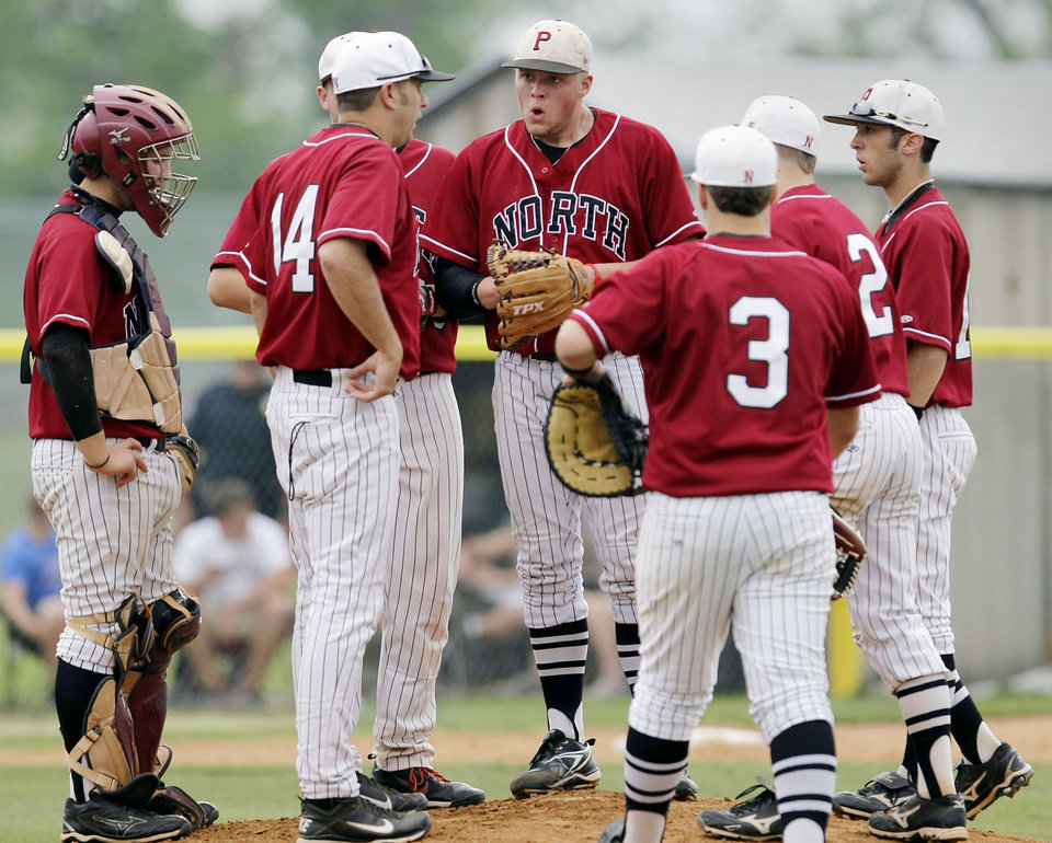 With bases loaded and no outs, Putnam City North starting pitcher Jace James (center) gets a mound conference in the 2nd inning of their game against Jenks in the 6A state high school baseball playoffs in Bixby, OK May 11, 2011. MICHAEL WYKE/Tulsa World