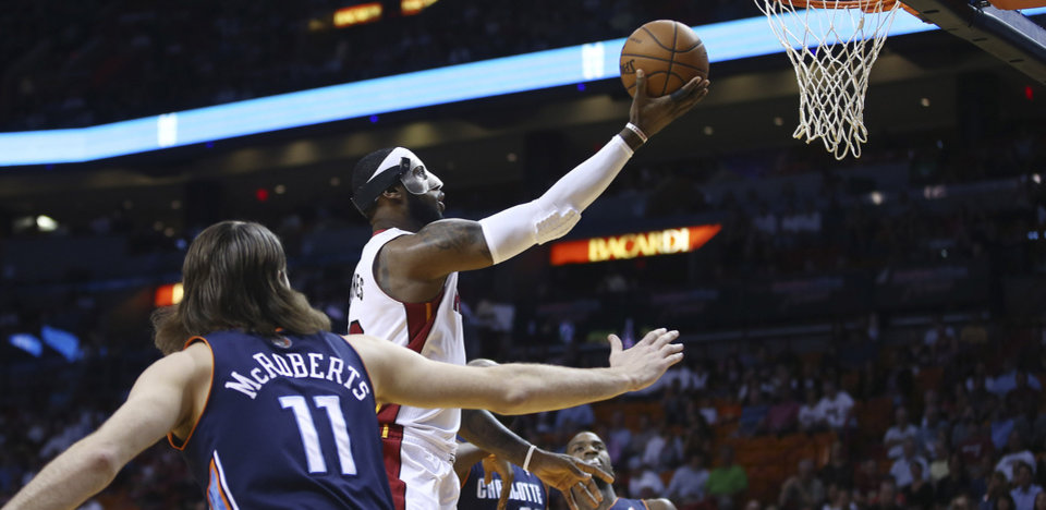 Photo - Miami Heat's LeBron James, center,  slides through Charlotte Bobcats players Michael Kidd-Gilchrist (14), Josh McRoberts (11) and Al Jefferson (25) for two points during the first half of an NBA basketball game in Miami, Monday, March 3, 2014. (AP Photo/J Pat Carter)