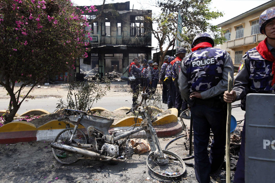 Myanmar police officers provide security near burnt buildings in Meikhtila, where Ethnic unrest between Buddhists and Muslims continues, in Mandalay division, about 550 kilometers (340 miles) north of Yangon, Myanmar, Friday, March. 22, 2013. Burning fires from two days of Buddhist-Muslim violence that killed at least 20 people smoldered across a central Myanmar town Friday as residents cowered indoors amid growing fears the country's latest bout of sectarian bloodshed could spread. The government's struggle to contain the unrest in Meikhtila is proving another major challenge President Thein Sein's reformist administration as it attempts to chart a path to democracy after nearly half a century of military rule that once crushed all dissent. (AP Photo/Khin Maung Win)