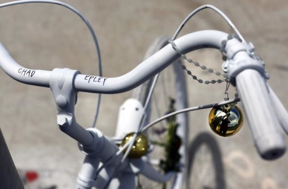 Photo -  A bicycle, painted white in its entirety, is chained to a pole at the intersection of NW 16 and Classen near the Plaza District where Chad Epley was killed after being hit by a vehicle while biking home from work at a local restaurant. The driver of that car fled the accident scene and police continue their search for the automobile and driver.  [JIM BECKEL/THE OKLAHOMAN]