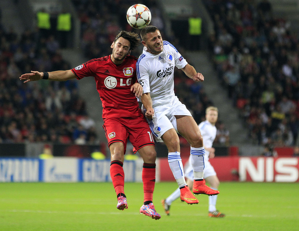 Photo - Leverkusen's Hakan Calhanoglu, left, and Copenhagen's Bashkim Kadrii challenge for the ball during the Champions League qualifying soccer match between Bayer 04 Leverkusen and FC Copenhagen in Leverkusen, Germany, Wednesday, Aug. 27, 2014. (AP Photo/Frank Augstein)