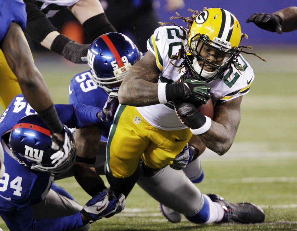 Green Bay Packers running back Alex Green (20) is tackled by New York Giants' Michael Boley (59) and Mathias Kiwanuka (94) during the first half of an NFL football game, Sunday, Nov. 25, 2012, in East Rutherford, N.J. (AP Photo/Kathy Willens)