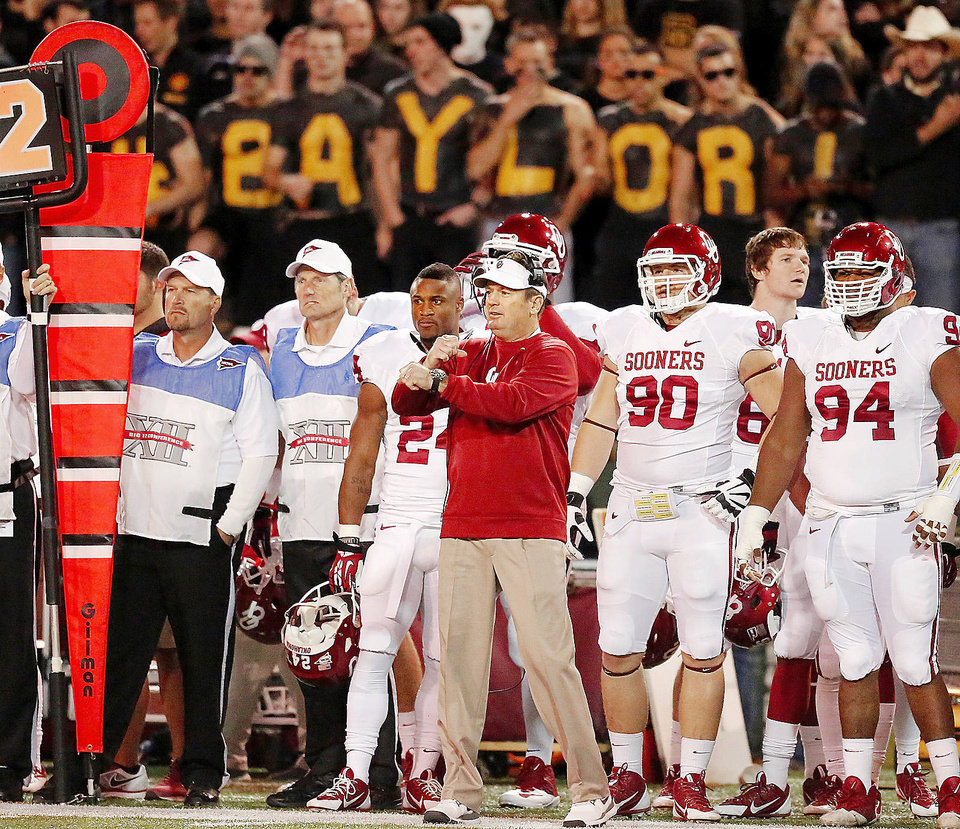 Photo - OU coach Bob Stoops signals to his players during last week's loss to Baylor in Waco, Texas.  Photo by Jim Beckel, The Oklahoman