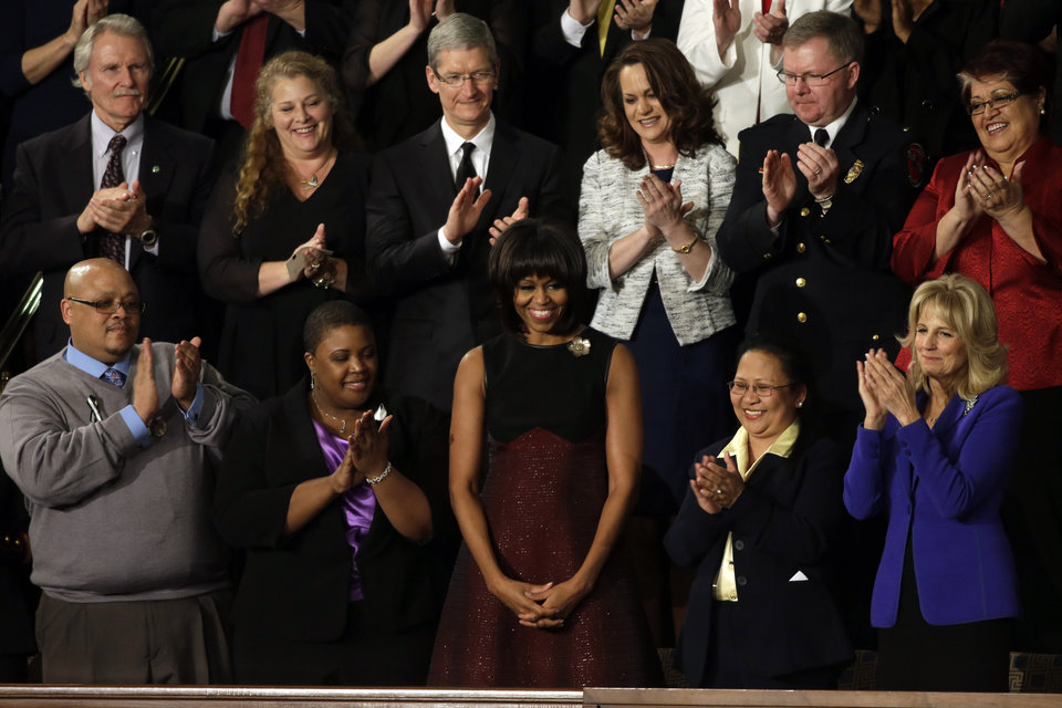 Photo - First lady Michelle Obama is applauded before President Barack Obama's State of the Union address during a joint session of Congress on Capitol Hill in Washington, Tuesday Feb. 12, 2013. Front row, from left are, Nathaniel Pendleton, Cleopatra Cowley-Pendleton, Mrs. Obama, Menchu Sanchez and Jill Biden. Second row, from left are, Oregon Gov. John Kitzhaber, Deb Carey, Apple CEO Tim Cook, Amanda McMillan, Lt. Brian Murphy and Marie Lopez Rogers. (AP Photo/Jacquelyn Martin)