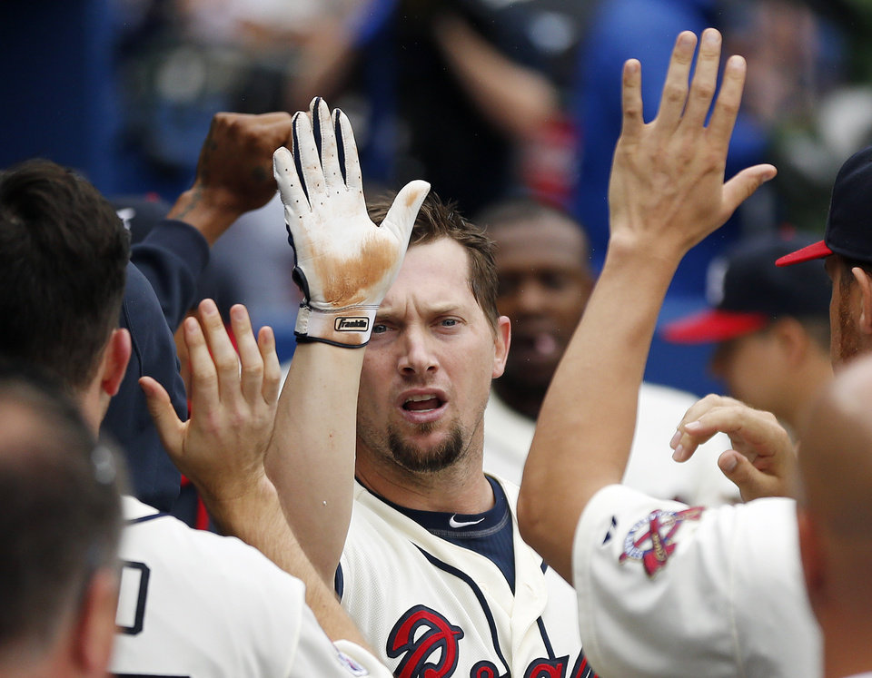 Photo - Atlanta Braves third baseman Chris Johnson, center, celebrates in the dugout after hitting a two-run home run in the second inning of a baseball game against the Philadelphia Phillies in Atlanta, Sunday, July 20, 2014.(AP Photo/John Bazemore)