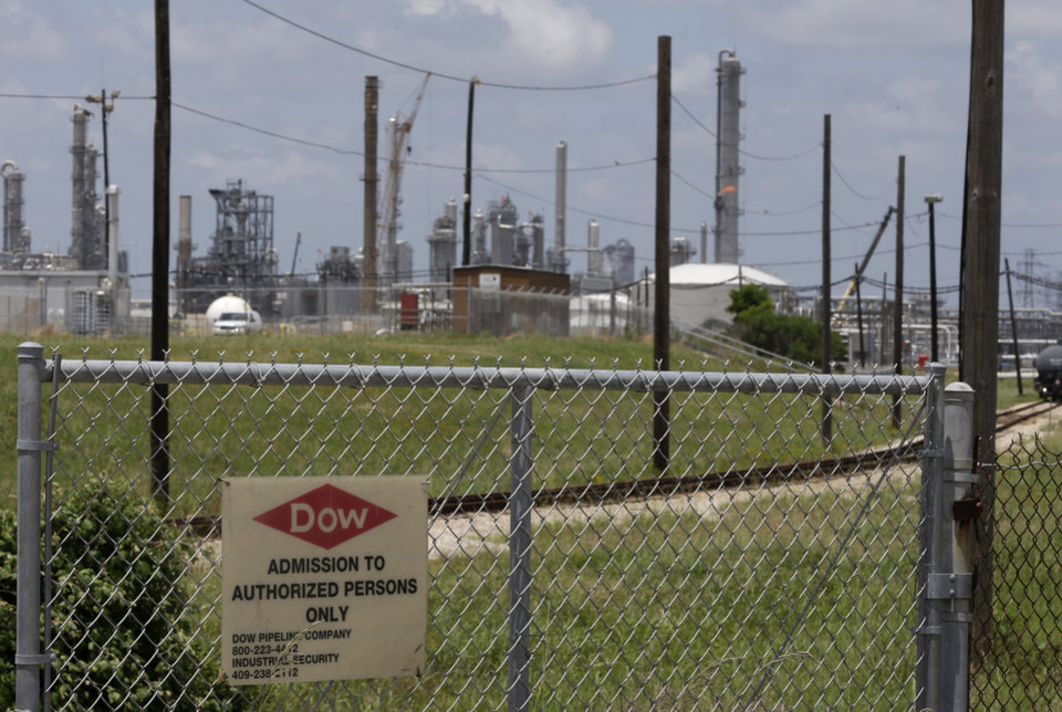 Photo - In this May 22, 2014 photo, a sign is posted on a roadside fence outside a Dow Chemicals plant in Freeport, Texas. The plan from Dow Chemical and the Nature Conservancy calls for growing thick groves of trees to capture pollutants downwind from a chemical plant. (AP Photo/Pat Sullivan)