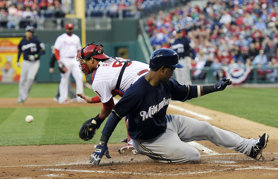 Photo - Milwaukee Brewers' Jean Segura, right, slides into home plate and score a run in front of Philadelphia Phillies' catcher Carlos Ruiz on an Aramis Ramirez RBI-single during the first inning of a baseball game on Wednesday, April 9, 2014, in Philadelphia. (AP Photo/Michael Perez)
