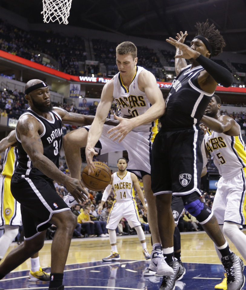 Indiana Pacers forward Tyler Hansbrough, center, looses a rebound between Brooklyn Nets forwards Reggie Evans, left, and Gerald Wallace in the first half of an NBA basketball game in Indianapolis, Monday, Feb. 11, 2013.  (AP Photo/Michael Conroy)