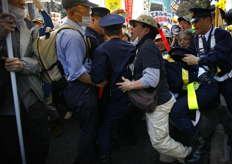 Photo - A protester scuffles with police officers during an anti-nuclear demonstration in Tokyo, Saturday, March 9, 2013. Gathering on a weekend ahead of the second anniversary of the March 11 quake and tsunami that sent Fukushima Dai-ichi plant into multiple meltdowns, demonstrators said they would never forget the world's worst nuclear catastrophe, and expressed alarm over the government's eagerness to restart reactors. (AP Photo/Junji Kurokawa)