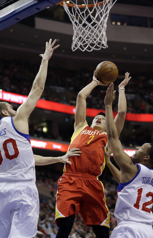 Houston Rockets' Jeremy Lin, center, goes up for a shot between Philadelphia 76ers' Spencer Hawes, left, and Evan Turner in the first half of an NBA basketball game, Saturday, Jan. 12, 2013, in Philadelphia. (AP Photo/Matt Slocum)