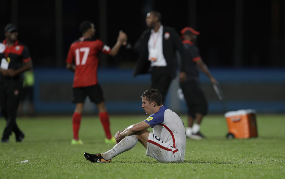 Photo -  Matt Besler, squats on the field after the United States lost 2-1 to Trinidad and Tobago last October, costing the U.S. a spot in the World Cup. [AP PHOTO]