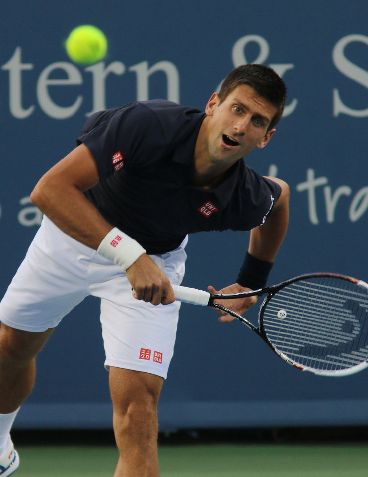 Photo - Novak Djokovic, of Serbia, serves to Gilles Simon, of France, at the Western & Southern Open tennis tournament, Tuesday, Aug. 12, 2014, in Mason, Ohio. (AP Photo/Tom Uhlman)
