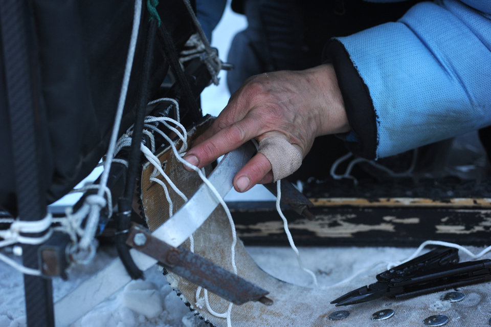 Photo - Martin Buser changes his drag brake onto his coast sled. Buser has his finger taped up because it keeps popping out of joint. Buser was second into the Unalakleet checkpoint during the 2014 Iditarod Trail Sled Dog Race on Saturday, March 8, 2014. (AP Photo/The Anchorage Daily News, Bob Hallinen)