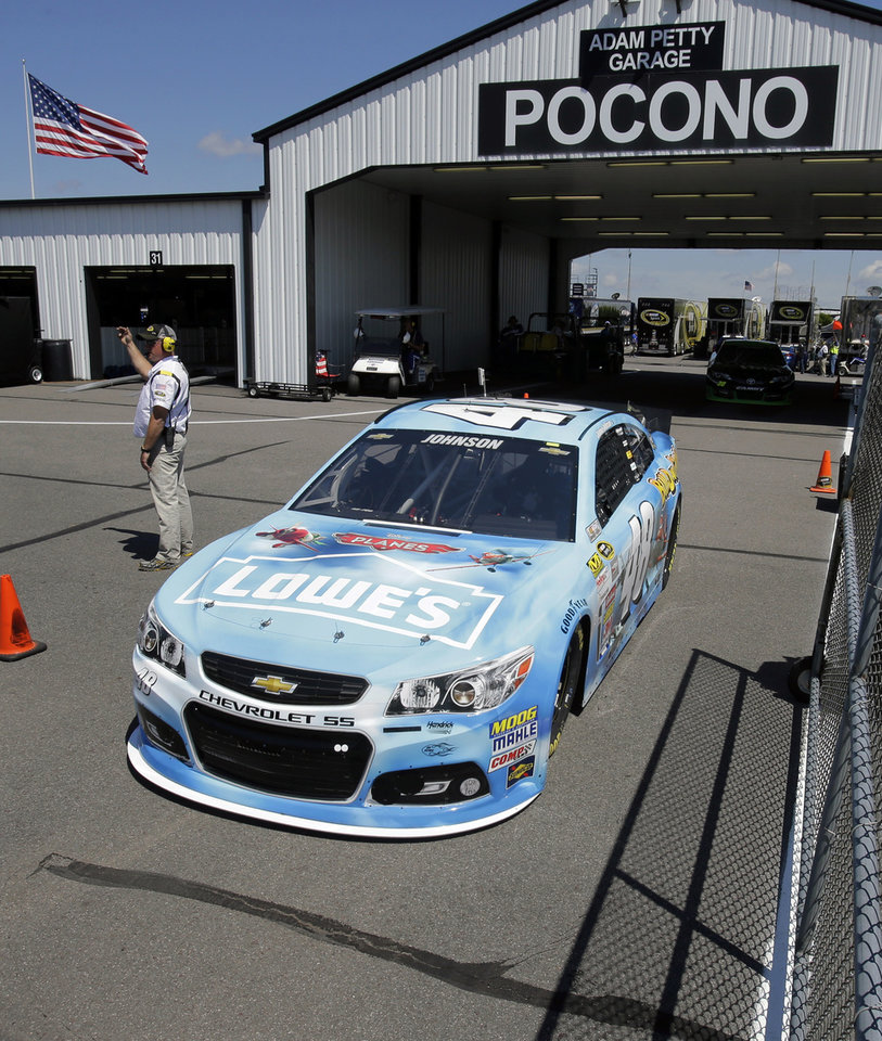 Photo - Jimmie Johnson drives in the garage area during practice Friday Aug. 2, 2013, for Sunday's NASCAR Sprint Cup Series auto race in Long Pond, Pa. (AP Photo/Mel Evans)