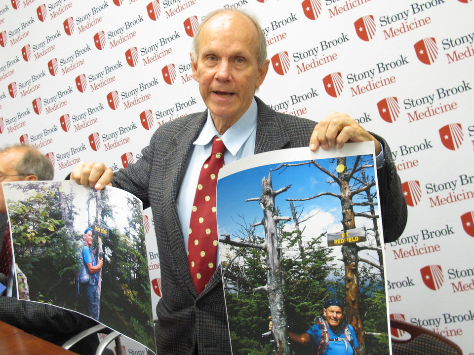 Stony Brook University professor Michael T. Vaughan holds up photographs he took during a summer camping trip as he speaks with reporters at Stony Brook University Hospital in Stony Brook, N.Y. on Friday, Oct. 12, 2012. Doctors are awaiting test results to confirm whether Vaughan may have contracted the hantavirus during the camping trip. (AP Photo/Frank Eltman)