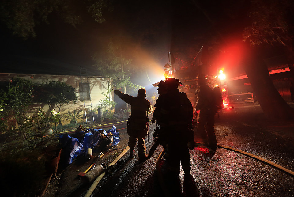 Fire crews respond to a wind driven vegetation fire that damaged this home on  Highway 128 early Wednesday May 1, 2013 in Knights Valley, Calif.  Crews battled two small wildfires on Wednesday in California wine country that were pushed by gusty winds. (AP Photo/The Press Democrat, Kent Porter)