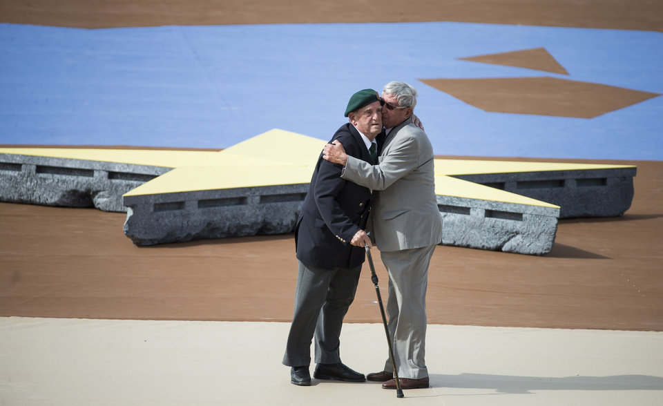 Photo - French WWII veteran Leon Gautier of the Kiieffer commando, left, and German WWII veteran, paratrooper Johannes Borner, embrace as a sign of reconciliation during an international ceremony marking the 70th anniversary of the Allied landings on D-Day on Sword Beach in Ouistreham, in Normandy, France, Friday, June 6 June 2014. World leaders and veterans gathered by the beaches of Normandy on Friday to mark the 70th anniversary of World War Two's D-Day landings. (AP Photo/Ian Langsdon, Pool)