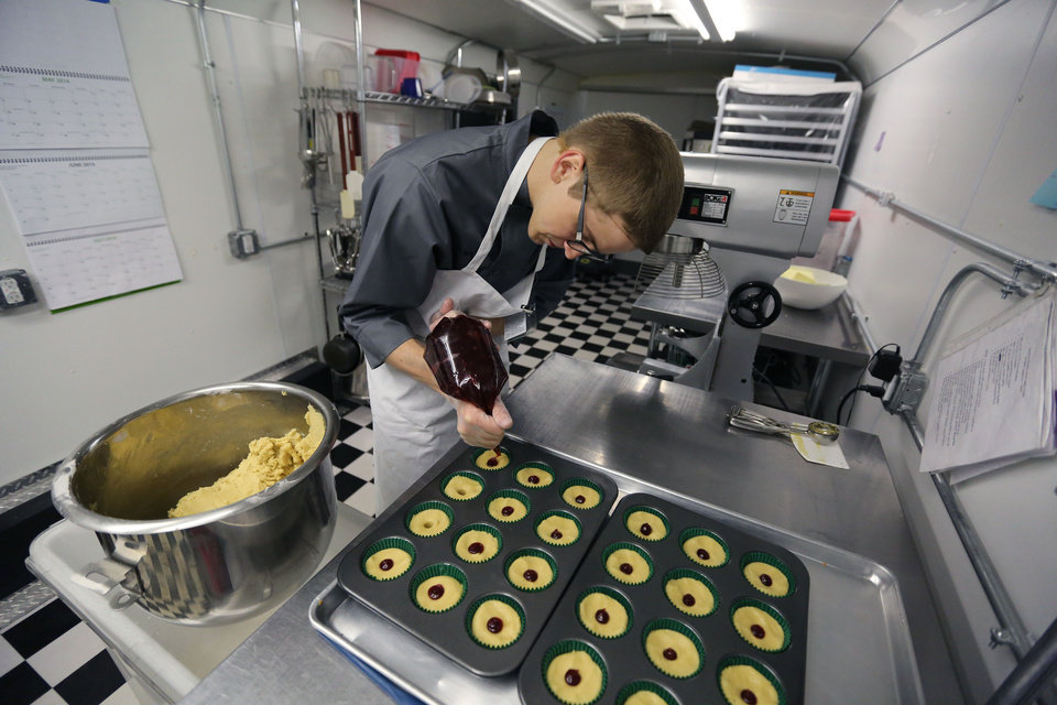 Photo - In this June 19, 2014 photo, chef Alex Tretter adds strawberry jam to cannabis-infused peanut butter and jelly cups before baking them, at Sweet Grass Kitchen, a well-established gourmet marijuana edibles bakery which sells its confections to retail outlets, in Denver. Sweet Grass Kitchen, like other cannabis food producers in the state, is held to rigorous health inspection standards, and has received praise from inspectors, according to owner Julie Berliner. (AP Photo/Brennan Linsley)