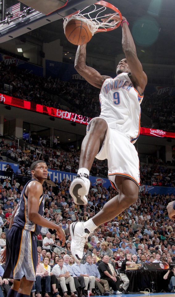 Photo - Oklahoma City's Serge Ibaka dunks the ball as Rudy Gay of Memphis watches during the NBA basketball game between the Oklahoma City Thunder and the Memphis Grizzlies at the Ford Center in Oklahoma City on Wednesday, April 14, 2010.   Photo by Bryan Terry, The Oklahoman ORG XMIT: KOD