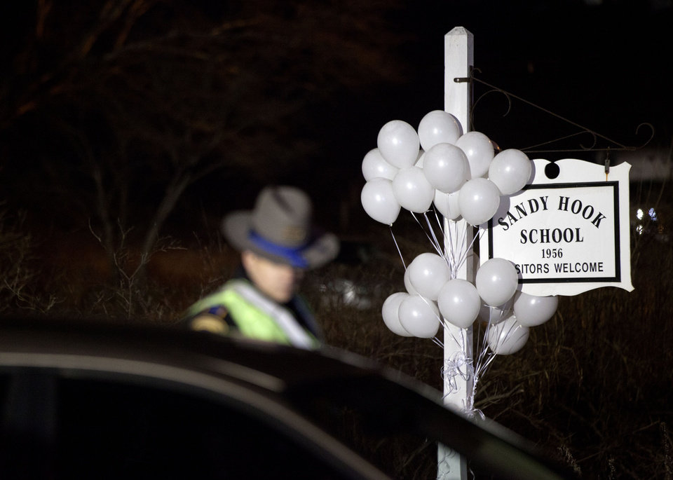Photo - White balloons decorate the sign for the Sandy Hook Elementary School as a Connecticut State Trooper stands guard at the school's entrance, Saturday, Dec. 15, 2012, in Newtown, Conn. A gunman killed his mother at their home and later walked into Sandy Hook Elementary School Friday and opened fire, killing 26 people, including 20 children. (AP Photo/David Goldman)