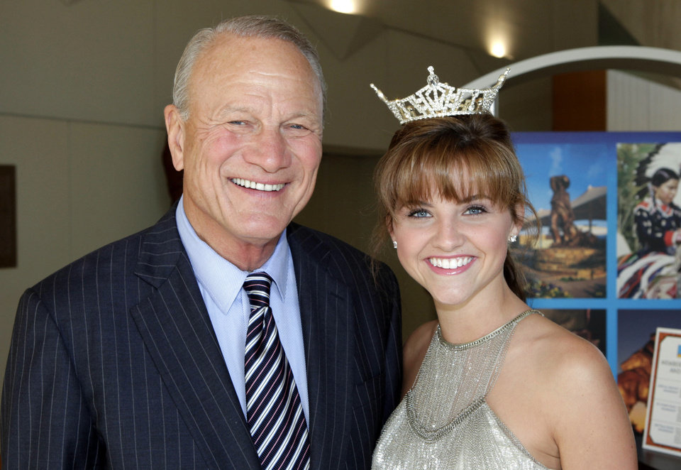 Barry Switzer and Georga Frazier, Miss Okmulgee County, at the Oklahoma Sports Hall of Fame Banquet, Monday, August 5, 2013. Photo by David McDaniel, The Oklahoman