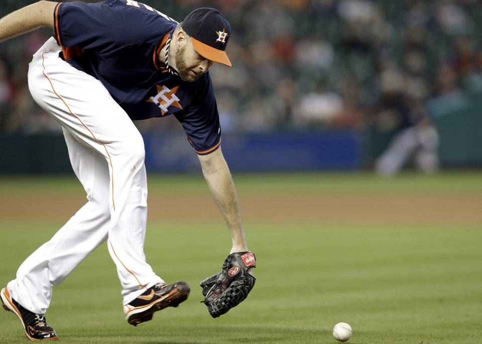 Photo - Houston Astros starting pitcher Scott Feldman cannot get to the ball in time, giving Los Angeles Angels' Josh Hamilton a single, in the fourth inning of a baseball game on Sunday, April 6, 2014, in Houston. (AP Photo/Pat Sullivan)