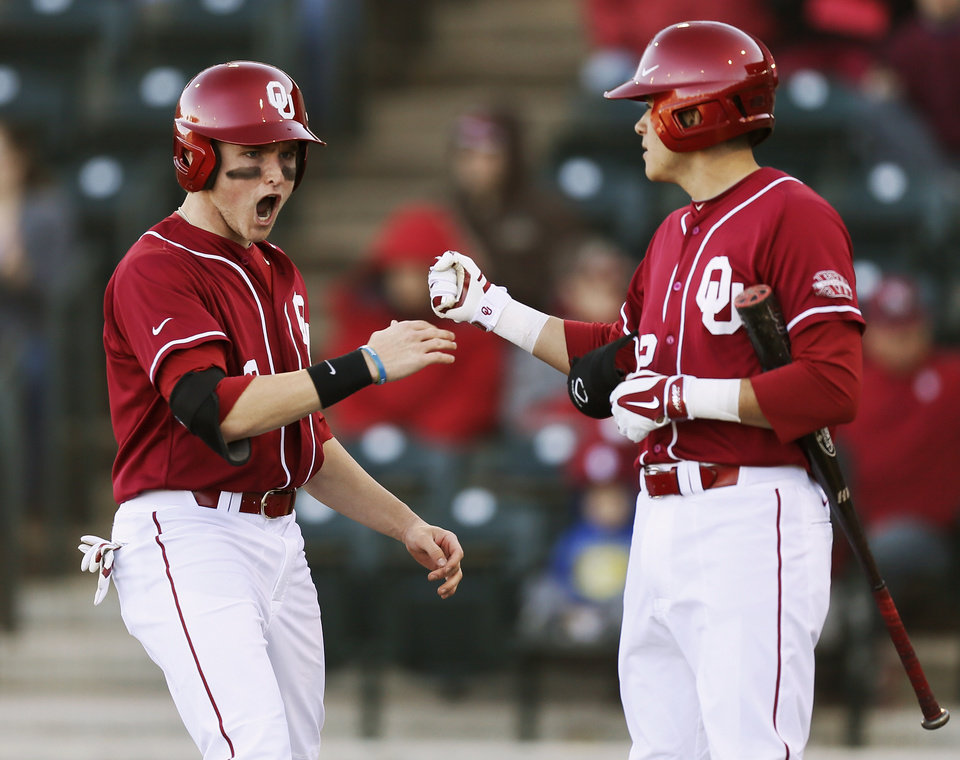 Oklahoma's Craig Aikin (3), left, celebrates with Hector Lorenzana (12) after scoring in the fifth inning during OU's season-opening college baseball game against Seton Hall at L. Dale Mitchell Park in Norman,  Okla., Friday, Feb. 14, 2014. Photo by Nate Billings, The Oklahoman