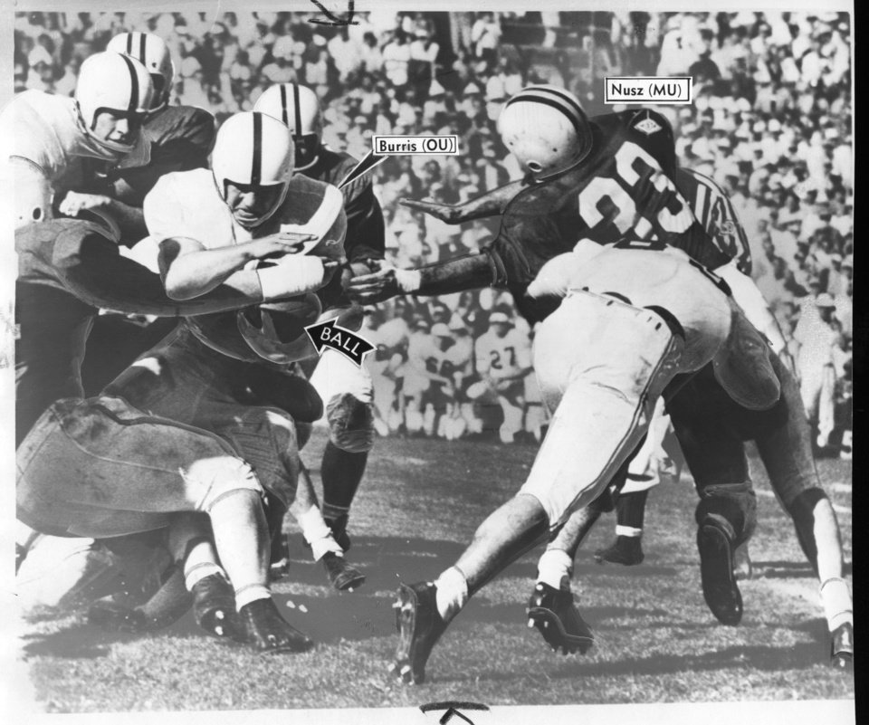 "Photo - FOOTBALL OU ORANGE BOWL 1956 / UNIVERSITY OF OKLAHOMA: Caption reads "" Bob Burris plows through the Maryland opposition for seven-yard gain during 2nd quarter as Terp Dave Nusz is cut off.""  Date photo was taken is unknown. Photo was published in the Oklahoma City Times on 1-3-1956."
