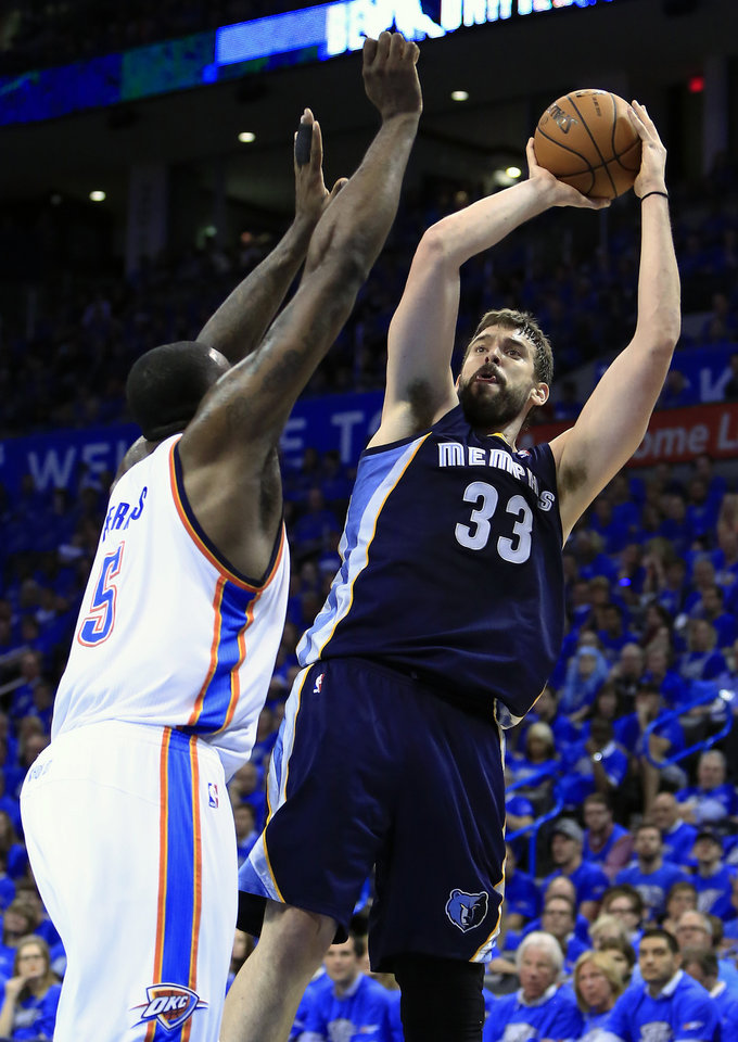 Photo - Memphis Grizzlies center Marc Gasol (33) shoots as Oklahoma City Thunder center Kendrick Perkins (5) defends during the second quarter of Game 1 of the opening-round NBA basketball playoff series in Oklahoma City on Saturday, April 19, 2014. (AP Photo/Alonzo Adams)