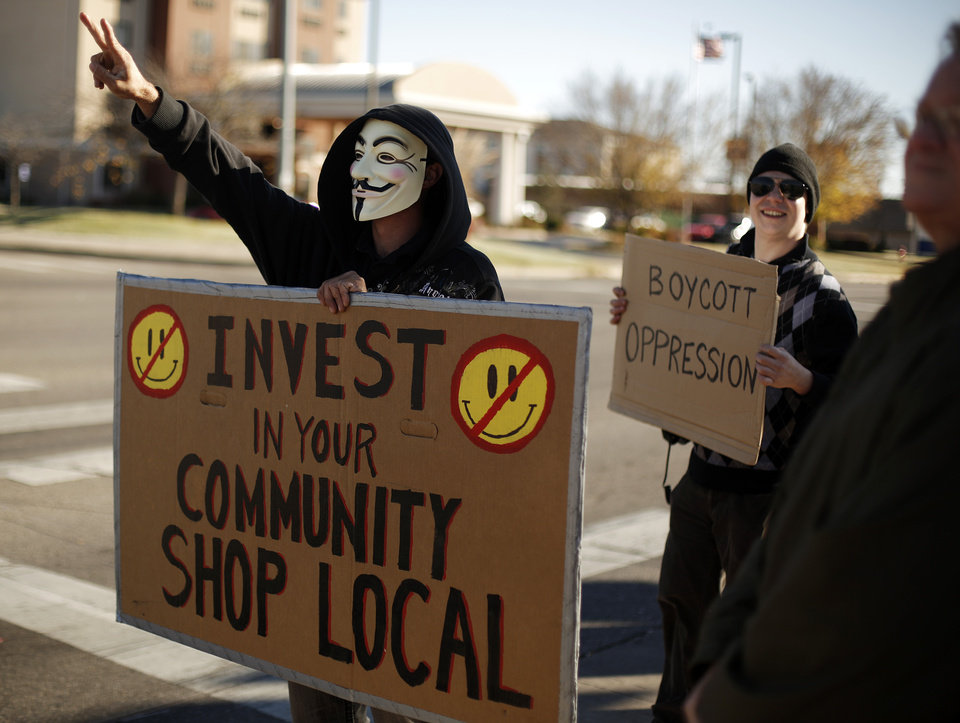 Rib Shawnee (left) and Thants Peterson stand with signs during an Occupy OKC demonstration at a Wal-Mart in Del City, Friday, Nov. 23, 2012.  Members of the Occupy movement were protesting for Wal-Mart worker's rights to a living wage.  Photo by Garett Fisbeck, The Oklahoman