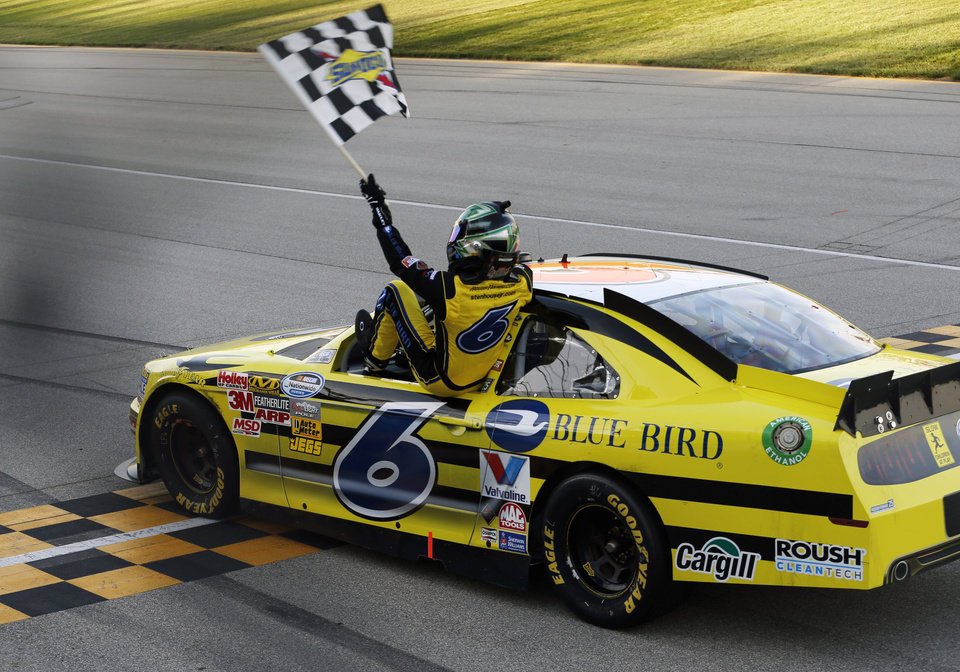Photo -   Ricky Stenhouse Jr. (6) get back into his car with the checkered flag after winning the NASCAR Nationwide Series auto race at Chicagoland Speedway in Joliet, Ill., Saturday, Sept. 15, 2012. (AP Photo/Tim Stewart)