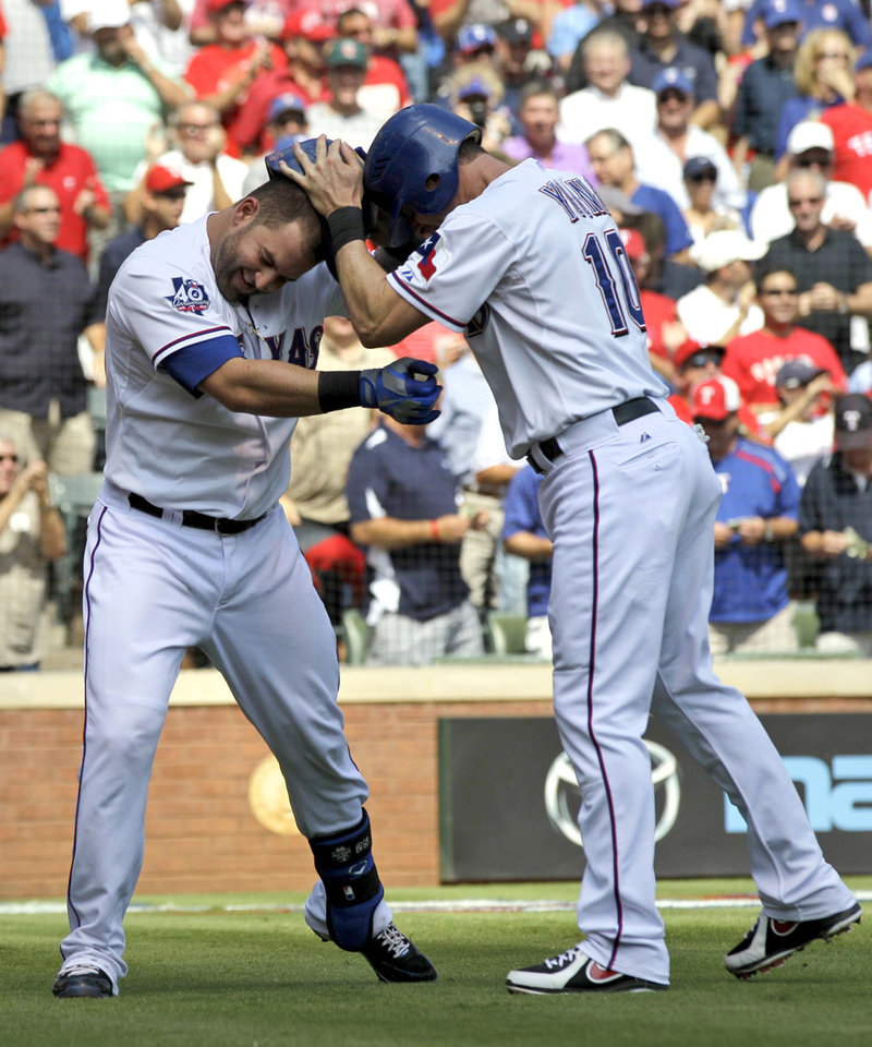 Photo -   Texas Rangers' Mike Napoli, left, is congratulated by Michael Young (10) after Napoli's two-run home run that scored Young off a pitch from Oakland Athletics' Travis Blackley in the first inning of a baseball game, Thursday, Sept. 27, 2012, in Arlington, Texas. (AP Photo/Tony Gutierrez)