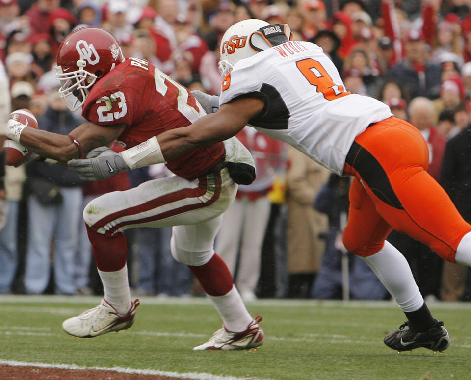 Photo - Oklahoma's Allen Patrick (23) scores a touchdown past Oklahoma State's Donovan Woods (8) during the first half of the college football game between the University of Oklahoma Sooners (OU) and the Oklahoma State University Cowboys (OSU) at the Gaylord Family-Memorial Stadium on Saturday, Nov. 24, 2007, in Norman, Okla. 