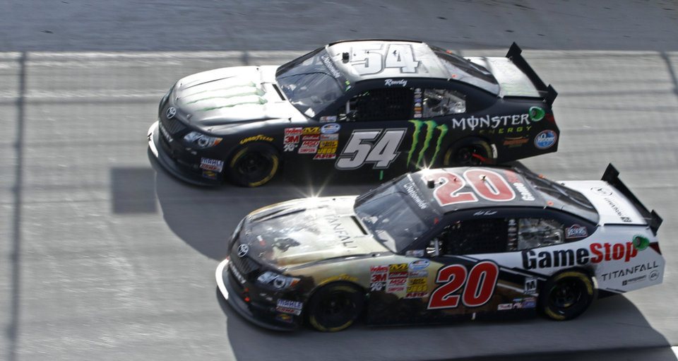 Photo - Kyle Busch (54) races with Matt Kenseth (20) during the NASCAR Nationwide Series auto race at Bristol Motor Speedway on Saturday, March 15, 2014, in Bristol, Tenn. Busch won the race. (AP Photo/Wade Payne)