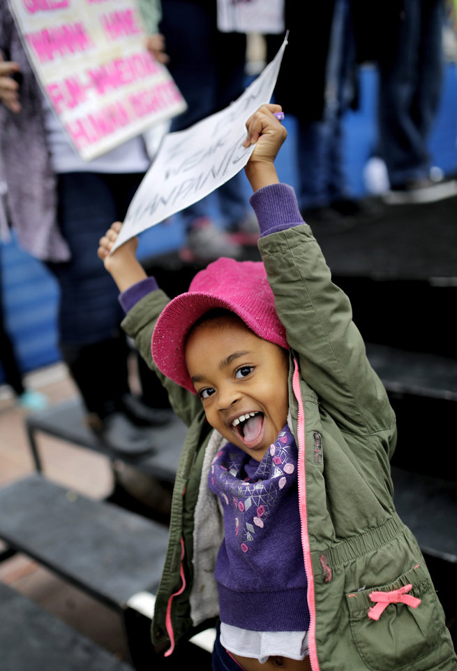 Photo - Savahli Liger, 4, of Oklahoma City, waves her sign back and forth above her head near the stage. Her mother was one of the speakers to address the crowd. A crowd estimated by organizers to be as many as 7,000 people came to the state Capitol in Oklahoma City Saturday, Jan. 21, 2017, to rally, using their voices and signs to express displeasure with the nation's new administration as part of a larger network of marches taking place across the country following Donald Trump's inauguration.   The Women's March on Oklahoma included a walk along Lincoln Blvd., with the Capitol as a backdrop, and a rally on the Capitol's south plaza that featured nearly a dozen speakers.  Photo by Jim Beckel, The Oklahoman