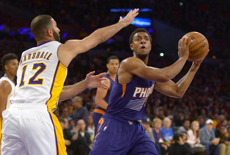 Photo - Los Angeles Lakers guard Kendall Marshall (12) guards Phoenix Suns guard Ish Smith (3) as he looks for the open in the first half of an NBA basketball game, Sunday, March 30, 2014, in Los Angeles.(AP Photo/Gus Ruelas)