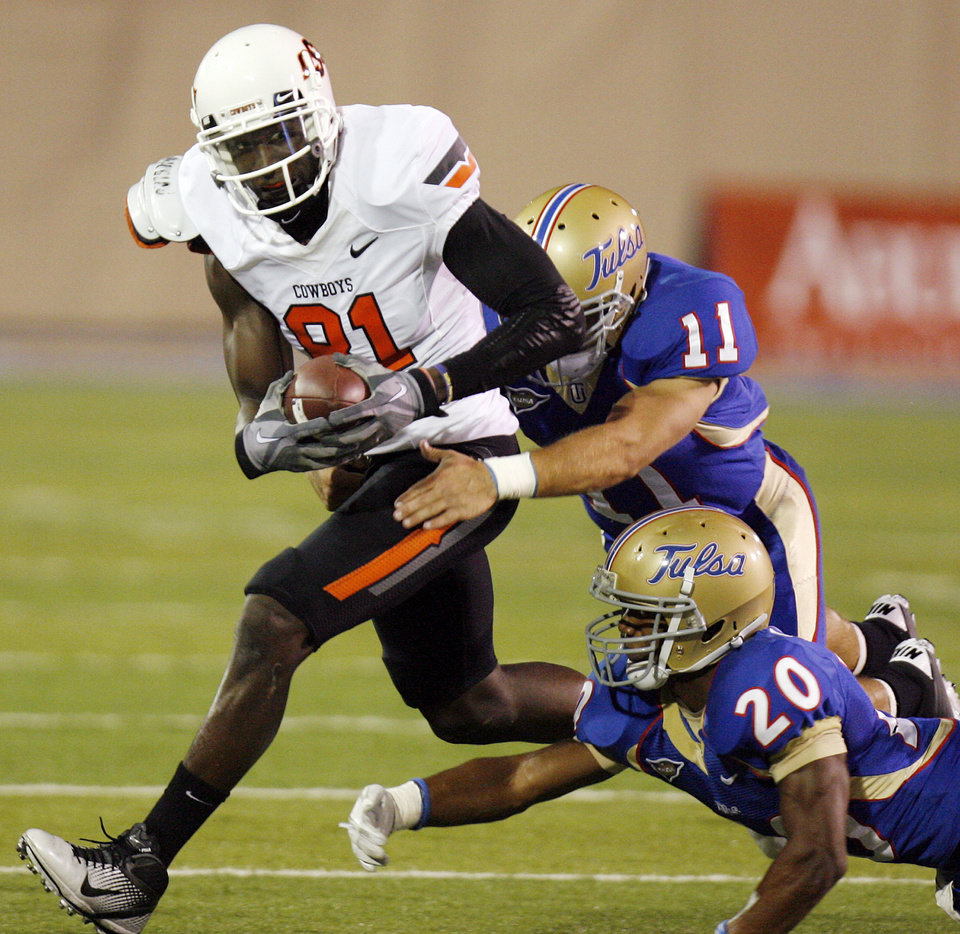 Photo - OSU's Justin Blackmon (81) is stopped after a catch by Alan Dock (11) and Marco Nelson (20) of TU in the first quarter during a college football game between the Oklahoma State University Cowboys and the University of Tulsa Golden Hurricane at H.A. Chapman Stadium in Tulsa, Okla., Sunday morning, Sept. 18, 2011. Photo by Nate Billings, The Oklahoman