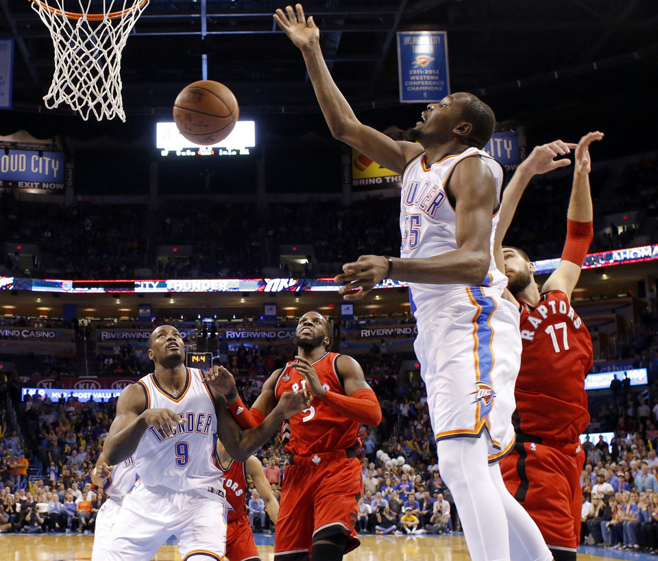 Photo - Oklahoma City's Kevin Durant (35) loses control of the ball as he goes to the basket between Toronto's DeMarre Carroll (5) and Jonas Valanciunas (17) during an NBA basketball game between the Oklahoma City Thunder and the Toronto Raptors at Chesapeake Energy Arena on Wednesday, Nov. 4, 2015. The Thunder lost 103-98. Photo by Bryan Terry, The Oklahoman