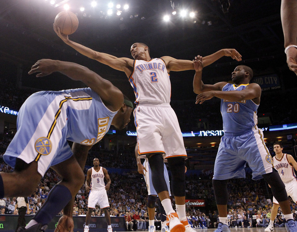 Oklahoma City's Thabo Sefolosha (2) fights Denver's Ty Lawson (3) and Raymond Felton (20) for a loose ball during the NBA basketball game between the Oklahoma City Thunder and the Denver Nuggets, Friday, April 8, 2011, at the Oklahoma City Arena.. Photo by Sarah Phipps, The Oklahoman
